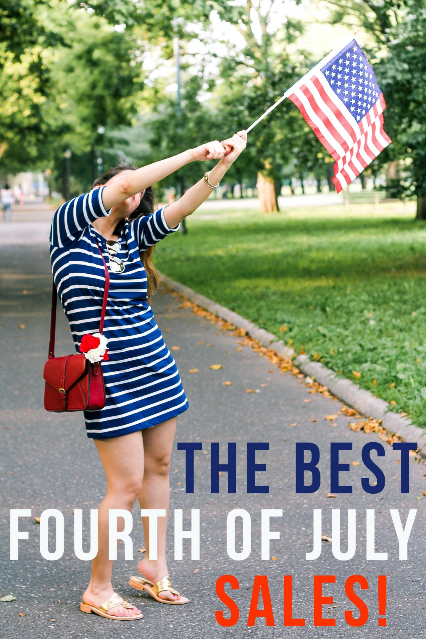 the best fourth of july sales wearing blue and white striped midi dress with red purse and golden jack rogers while holding an american flag.