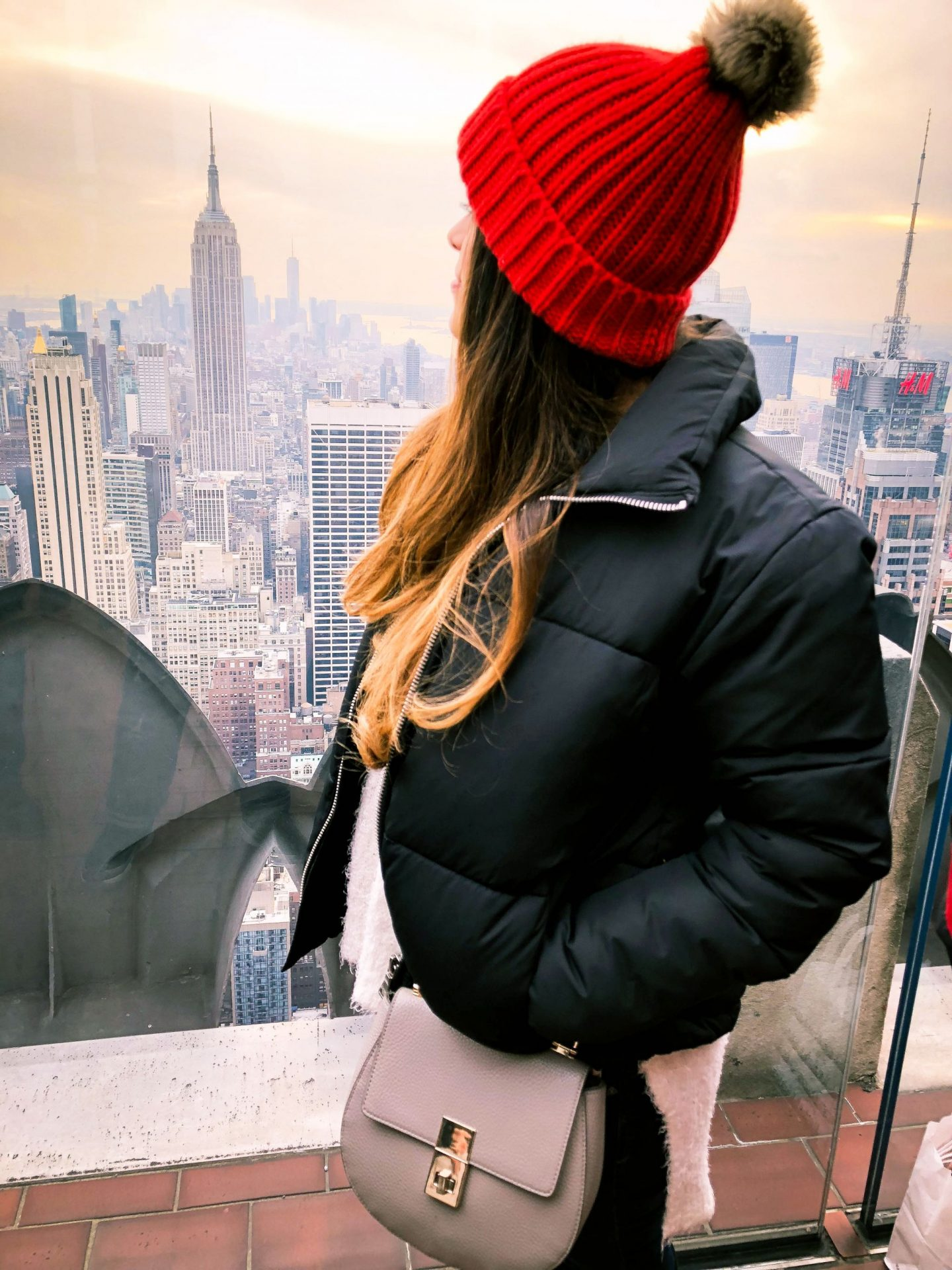 girl in puffer jacket and red pom hat on top of the rock in new york with view of the empire state building.